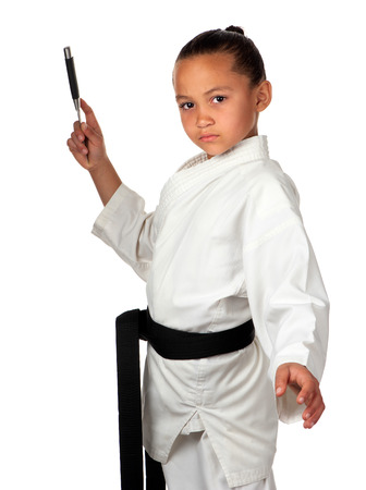 A young girl with black belt stands ready to throw a knife. Stock Photo