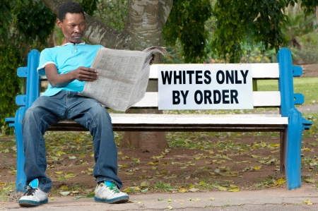 prejudice: A non-white man sits on a bench in a park reserved for whites. This was commonplace during the apartheid years in South Africa.