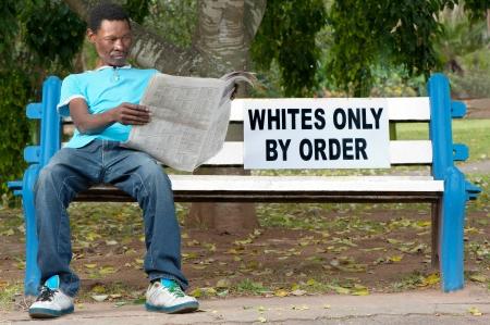 commonplace: Un uomo non-bianco si siede su una panchina in un parco riservato ai bianchi. Questo era comune durante gli anni dell'apartheid in Sud Africa.