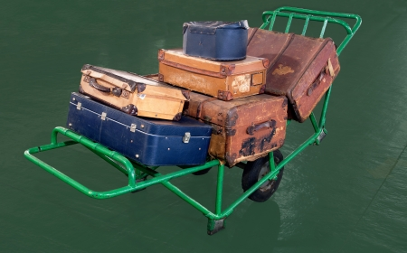 Very old and battered luggage are found on an old carrying trolley