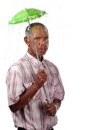 A pensioner attempts to wither the storm with a small umbrella, symbolizing poor retirement planning. Stock Photo