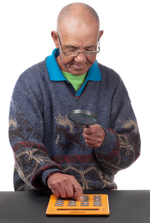 Poor vision forces an old man to see a calculator with the aid of glasses and magnifying glass