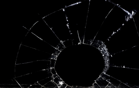 Shattered glass against a black backdrop is shown. Stock Photo