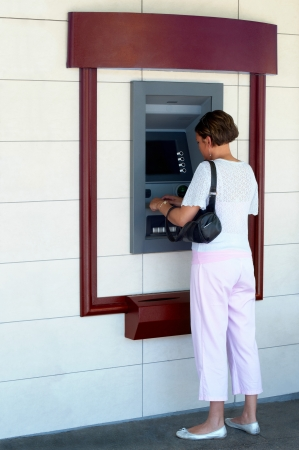 automatic machine: A woman performs a transaction at an ATM  Stock Photo