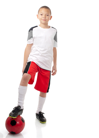 A young boy with togg on soccer ball is ready to play.