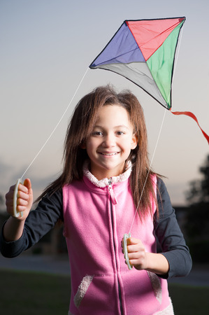 A jubilant young girl enjoys her kite as the sun is about to set.