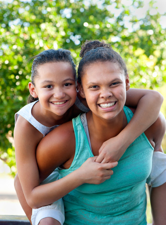 An older teenage girl carries a younger girl on her back, both smiling.