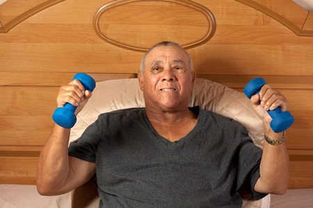 A frail senior citizen is supine but exercises with weights in his hands.