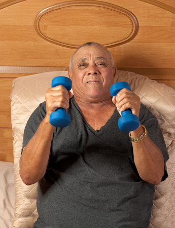 frail: A frail senior citizen is supine but exercises with weights in his hands.
