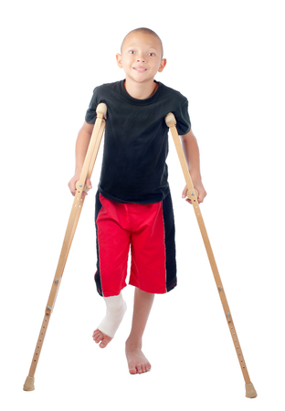 An injured boy with leg cast smiles bravely. Banque d'images