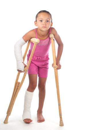 Een jong meisje worstelt om te lopen met krukken na verwondingen aan haar arm en been. Stockfoto
