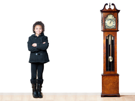 A young girl next to a grandfather clock indicates that growth takes time.