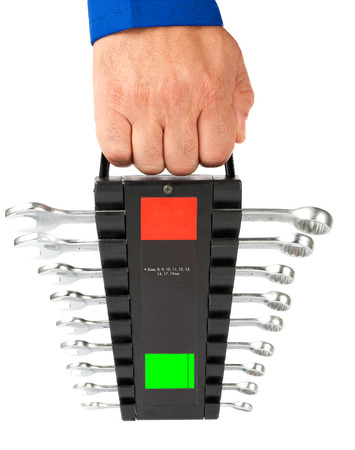 Spanners of different sizes are neatly carried by a worker.