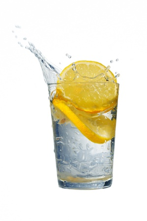 lemon water: Glass of fresh water with falling lemons isolated on white Stock Photo