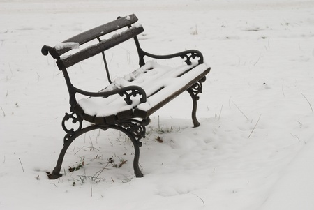 Old bench in park covered with snow