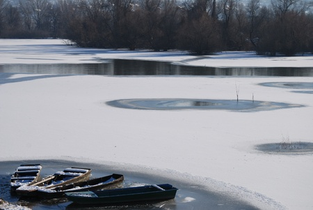 Winter landscape. Small frozen river and boats  on ice photo