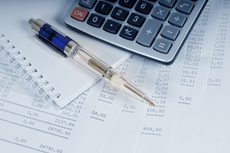 data sheet: Calculator and pen on sheets of banking report Stock Photo