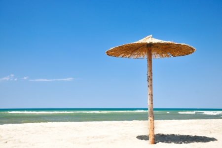 Tropical straw umbrella on a beautiful sand beach photo