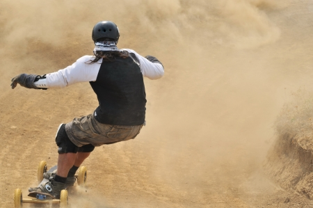 individual sport: Rear view at mountain boarder riding down through dust