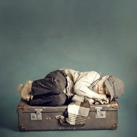 boy sleeping on a suitcase 스톡 콘텐츠