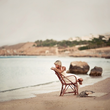 pensive woman sitting on the dunes watching the sea  스톡 콘텐츠