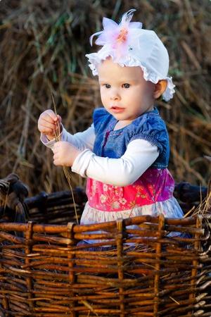 hayloft: little girl posing in a basket in the hayloft