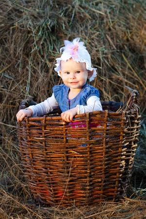 hayloft: ni�a posando en una canasta en el pajar Foto de archivo