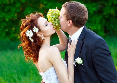 the bride and groom eat green grapes Stock Photo