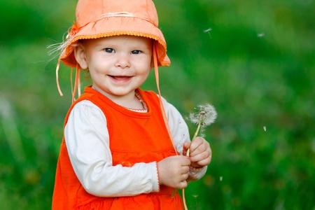 girl blowing seeds of a dandelion flower