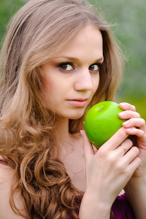 Beautiful girl with apple, against green summer garden. photo