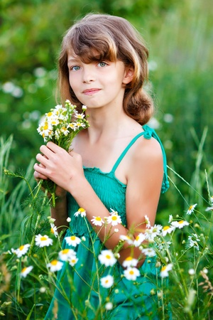 little girl in the field with flowers Stock Photo