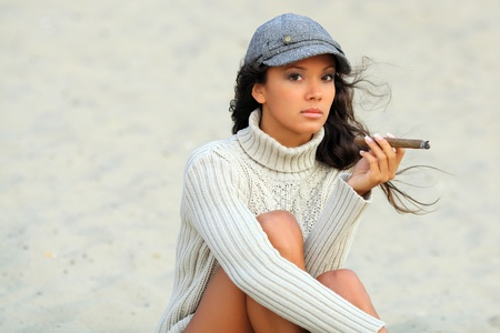 cigar smoking woman: beautiful young woman on the beach with a cigar