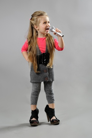 little girl singing karaoke on a gray background photo