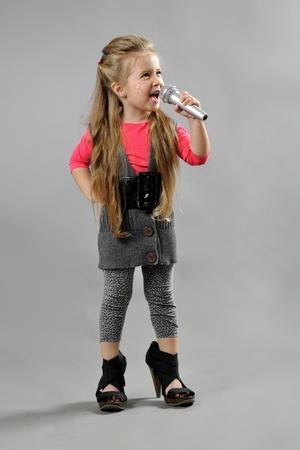 little girl singing karaoke on a gray background