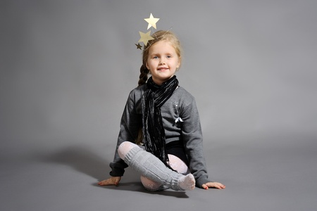 little girl dressed in the New Year on a gray background photo