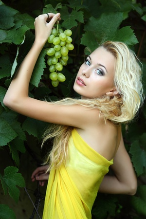 wine grower: portrait of a beautiful young blonde with a bunch of grapes Stock Photo