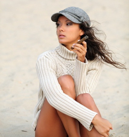 portrait of a beautiful girl with a cigar in the sand photo