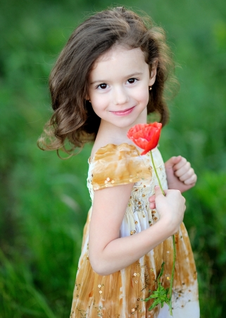 Portrait of Little girl with a flower poppy photo