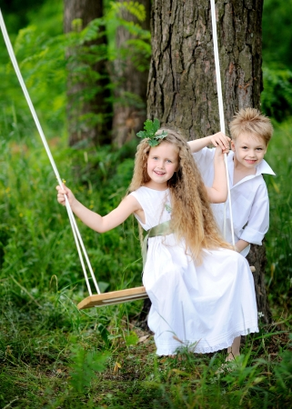 portrait of little boys and girls outdoors in summer photo