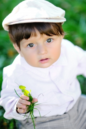 cute baby sitting in the grass outdoors  photo