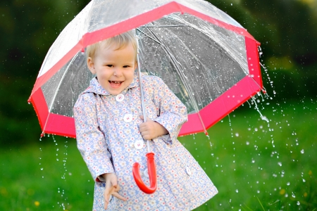 walking in the rain: portrait of a little girl with umbrella