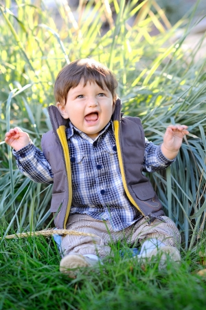 cute baby sitting in the grass outdoors in autumn jacket photo