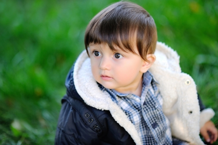 portrait of a baby boy outdoors in autumn jacket photo