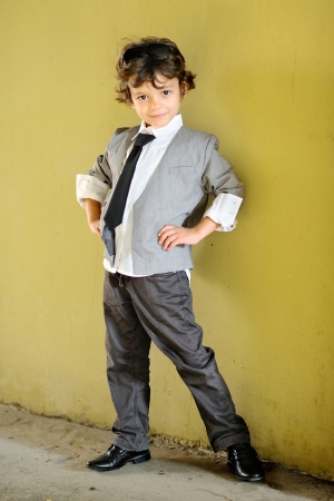 ni�o modelo: Retrato del ni�o peque�o con estilo al aire libre en un traje
