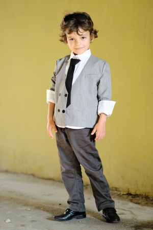 niño modelo: Retrato del niño pequeño con estilo al aire libre en un traje