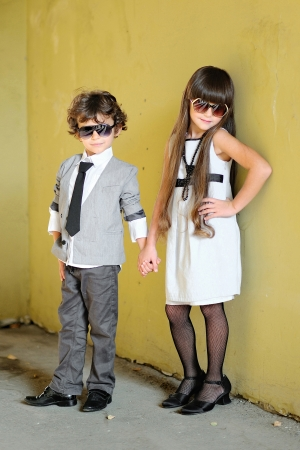 portrait of stylish little boy and girl outdoors