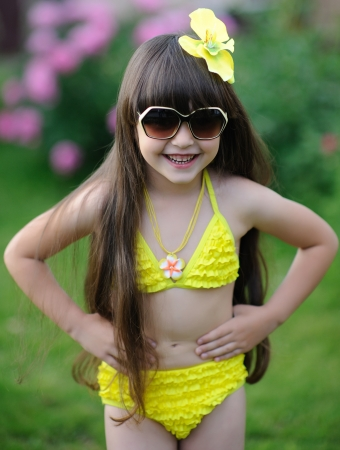 beach model: portrait of little girl outdoors in the tropical style