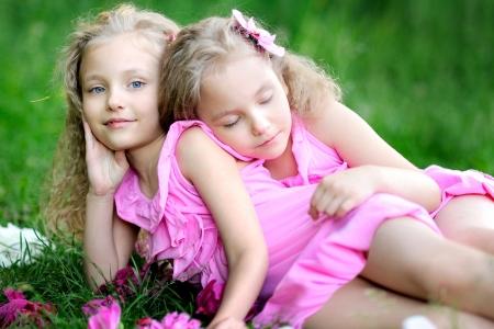 niñas sonriendo: Retrato de dos gemelos con peonías