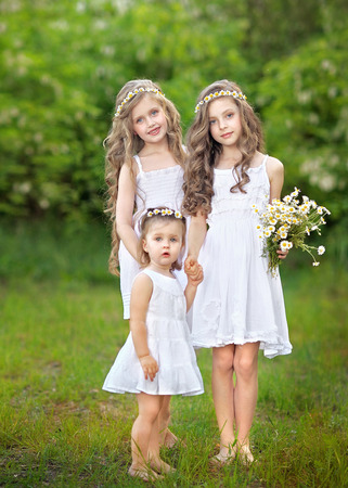 Portrait of three young girlfriends with daisies Stock Photo