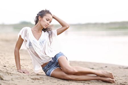 mojado: retrato de una hermosa joven en camisa mojada